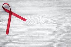 Rött band för HIV, HJÄLPMEDEL, drogmissbruk och anoreximedvetenhet på grå träcopyspace för bästa sikt för bakgrund Royaltyfri Fotografi