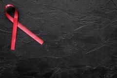 Rött band för HIV, HJÄLPMEDEL, drogmissbruk och anoreximedvetenhet på svart copyspace för bästa sikt för bakgrund Arkivbilder