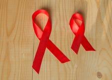 Rött band för medvetenhet på wood bakgrund: världsdagkamp mot HJÄLPMEDEL, befordringar till samhällsstöd för hälsan av Fotografering för Bildbyråer