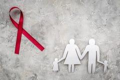 Rött band för near pappers- kontur för HIV, för HJÄLPMEDEL, för drogmissbruk och för anoreximedvetenhet av familjen på grå färgst Arkivbilder