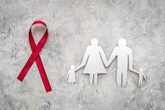 Rött band för near pappers- kontur för HIV, för HJÄLPMEDEL, för drogmissbruk och för anoreximedvetenhet av familjen på grå färgst royaltyfri foto