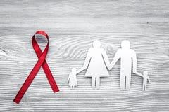 Rött band för near pappers- kontur för HIV, för HJÄLPMEDEL, för drogmissbruk och för anoreximedvetenhet av familjen på grått trä Royaltyfria Bilder
