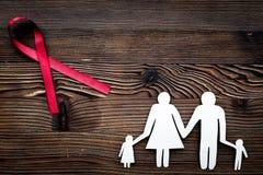 Rött band för near pappers- kontur för HIV, för HJÄLPMEDEL, för drogmissbruk och för anoreximedvetenhet av familjen på mörkt trä Fotografering för Bildbyråer