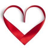 Rött band i en hjärtaform som isoleras på vit Arkivfoton