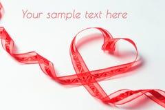 Rött band i form av hjärta med virvlar Royaltyfri Fotografi
