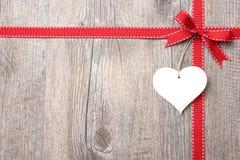 Rött band och pilbåge med hjärta Arkivfoto