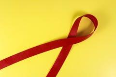 Rött band på en gul bakgrund Royaltyfria Bilder