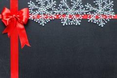 Rött band på en svart svart tavla med snöflingor Arkivbild