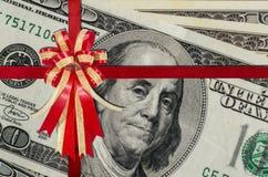 Rött band på grupp av US dollar för bakgrund Arkivfoton