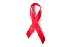 Rött band som symbolet av hjälpmedelmedvetenhet som isoleras på vit Arkivfoto
