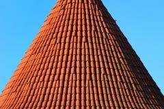 Rött belagt med tegel koniskt tak av ett torn fotografering för bildbyråer