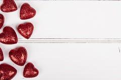 Rött blänka hjärtor på en vit träbakgrund Arkivfoton