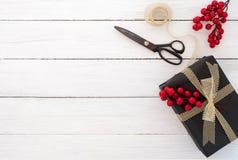 Rött boxas med pilbågen Räcka den tillverkade julklappgåvaasken och hjälpmedel på vit träbakgrund arkivfoto