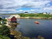 Rött fartyg, hus, grönt gräs, sommar i Peggys liten vik, Kanada Arkivfoton