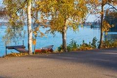 Rött fartyg och pont på kusten av sjön med blått vatten på en bakgrunds- och asfaltväg på en förgrund arkivfoto