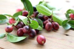 Rött fruktbär och gröna sidor på trägolv royaltyfri bild