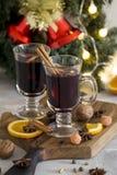 Rött funderat vin för jul i exponeringsglas på träbräde på vit bakgrund arkivbilder