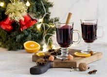 Rött funderat vin för jul i exponeringsglas på träbräde på vit bakgrund royaltyfri fotografi