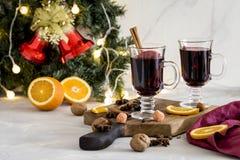 Rött funderat vin för jul i exponeringsglas på träbräde på vit bakgrund arkivfoton