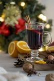 Rött funderat vin för jul i exponeringsglas på träbräde på vit bakgrund royaltyfri foto