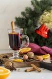 Rött funderat vin för jul i exponeringsglas på träbräde på vit bakgrund royaltyfri bild