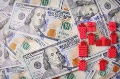 Rött gåvaband med pilbågen över amerikanska dollar Royaltyfri Foto
