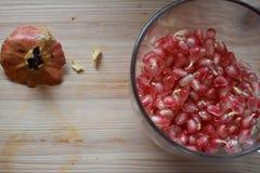 Rött granatäpplefrö i den glass bunken Arkivfoto