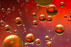 Rött, guld och lilor olja och bevattna abstrakt begrepp Royaltyfri Foto