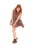 Rött haired flickaanseende i vind som isoleras över vit bakgrund Royaltyfria Bilder