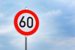 Rött hastighetsbegränsningtecken för runda 60km/h på huvudvägen framme av blå himmel royaltyfri fotografi