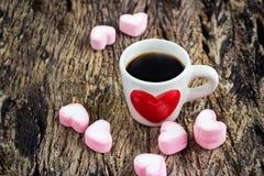 Rött hjärtaformsymbol på hjärta för kaffekopp och rosa färggodispå trälodisar royaltyfria foton