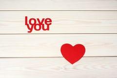 Rött hjärtasymbol på en wood bakgrund med inskriftförälskelseyo Royaltyfri Bild