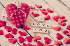 Rött hjärtatyg och trätext av ÄLSKAR JAG dig på trätabellbac Arkivfoto