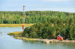 Rött hus i skog på stenig kust av Östersjön Arkivbilder