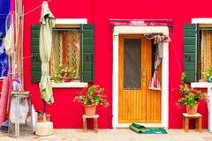Rött hus med blommor och växter Färgrikt hus i den Burano ön nära Venedig, Italien Arkivbilder