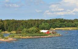Rött hus på stenig kust av Östersjön Royaltyfri Fotografi