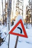 Rött indikera för tecken för triangelvägtrafik lämnade flyttning med flingor av snö, med gryningsolen på bakgrunden Jul fotografering för bildbyråer