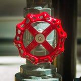 Rött industriellt ventilklapp på ett metallrör i en fabrik royaltyfri foto