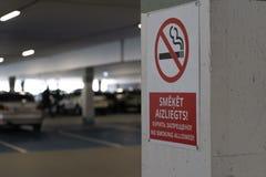 Rött inget - röka allower underteckna i tre språk i en underjordisk parkering med bilar som är synliga i bakgrunden royaltyfria bilder