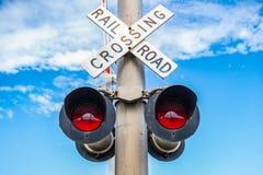 Rött järnvägkorsning tecken som vänds arkivbild