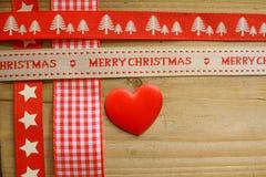 Rött julband och en förälskelsehjärta Arkivbild