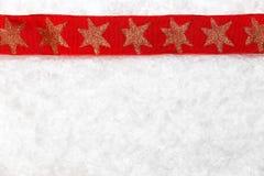 Rött julband på snöig bakgrund Arkivfoton
