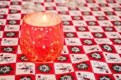 Rött julexponeringsglas dekorerade stearinljuset på en julduk Royaltyfria Foton