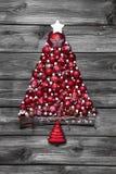 Rött julträd med bollar på gammal träsjaskig bakgrund royaltyfria foton