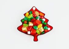 Rött keramiskt av ett julträd med godisar som isoleras i vit bakgrund arkivbild