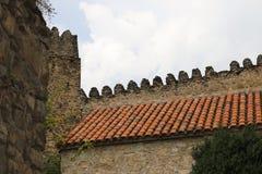 Rött keramiskt tak på stenhus royaltyfri bild