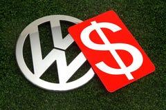 Rött kort med US dollartecknet på det Volkswagen emblemet Arkivbild