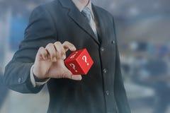 Rött kubik för för affärsmanhand och håll med frågefläcken arkivfoton