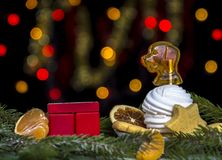 Rött kubkalenderdatum, platta av sötsaker med marshmallowen och karamell som hundbakgrund av gula och röda bokehljus arkivfoto