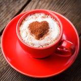 Rött kupa med cappuccino Arkivfoton